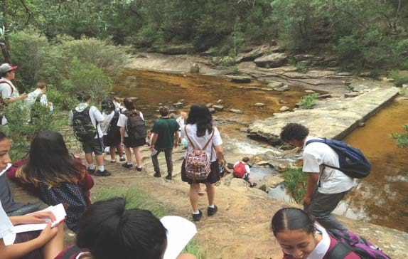 Students from CPAHS at Ingleburn Reserve standing alongside water.