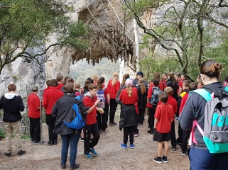 // Large number of students from OHS in uniform standing outside with surrounding trees and rock formations.