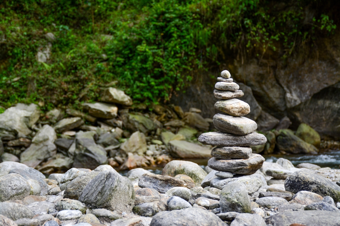 Stacked pile of small rocks sitting on a bed of rocks.