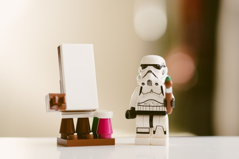 Lego figurine star trooper standing next to lego figurine easel..
