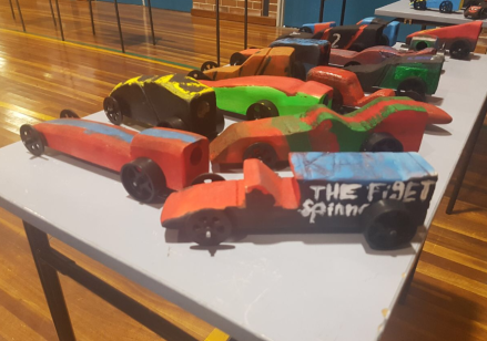 "13 miniature F1 race cars painted in different colours on table. Once race car has text ""The figet spinner"" written on its side."
