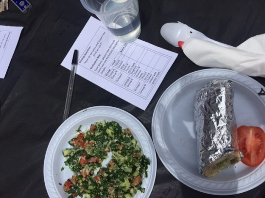 Plate of tabouli, plate with wrap and tomato, glass of water, spoon in napkin, pen, and grading sheet on table.