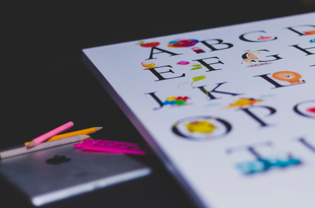 Alphabet book on right hand side. Left hand side has apple ipad with 3 coloured pencils atop.